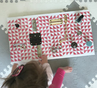 girl playing with a bright activity board on the floor