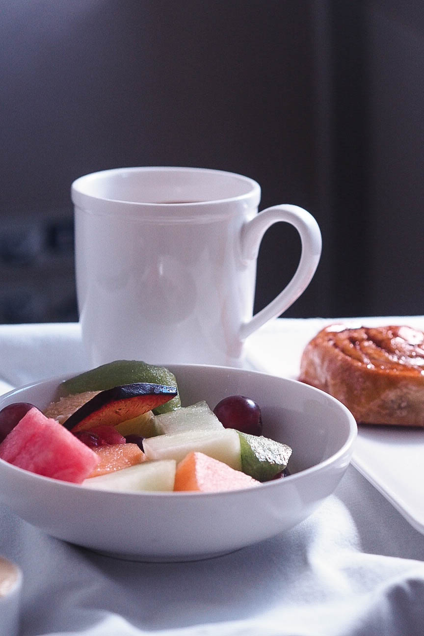 Cup of coffee, fresh fruit and pastry
