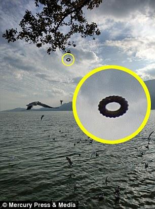 """Turista sorprendido al ver un """"OVNI en forma de rosquilla"""" flotando sobre un lago en una fotografía que tomó en China"""