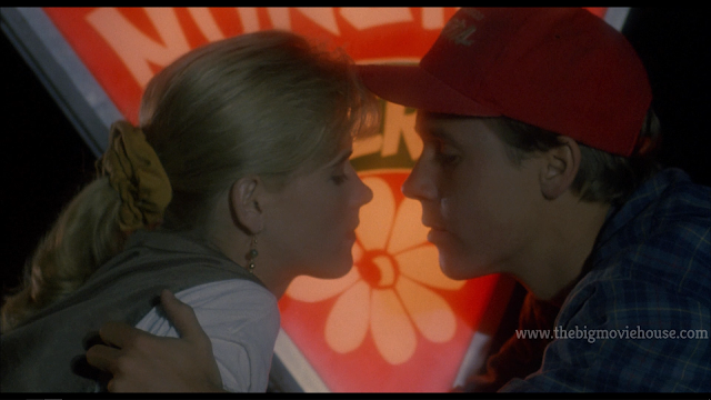two lovers kiss in front of a pizza sign