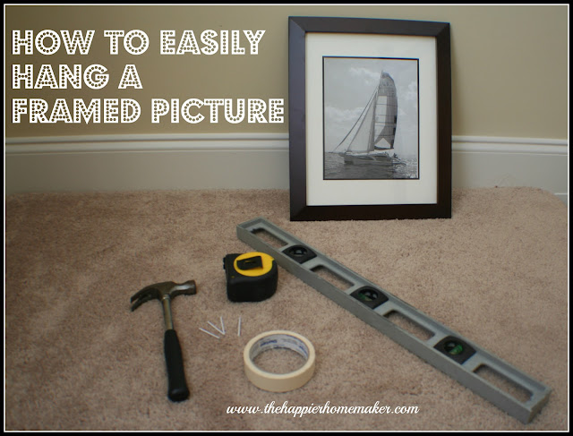 A brown picture frame of a sail boat with a level, hammer, tape measure, tape and nails for hanging the picture