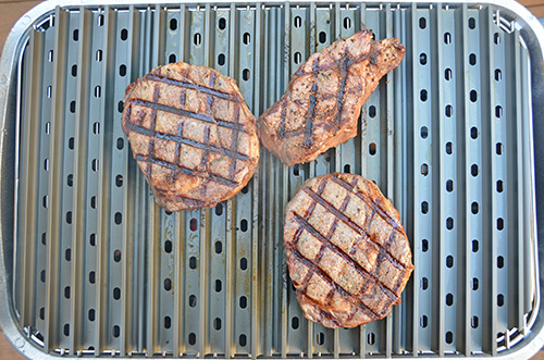 Ribeyes and a chuck eye steak grilling on the PK Grill.
