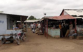 Bauernmarkt, wellblechgedeckte Stände mit Obst und Gemüse.