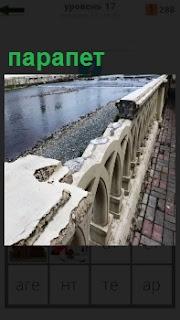 На набережной стоит ограждение парапет, но сломан в нескольких местах