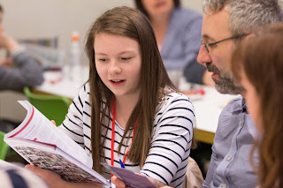 Student holding prospectus discussing with her parents university.