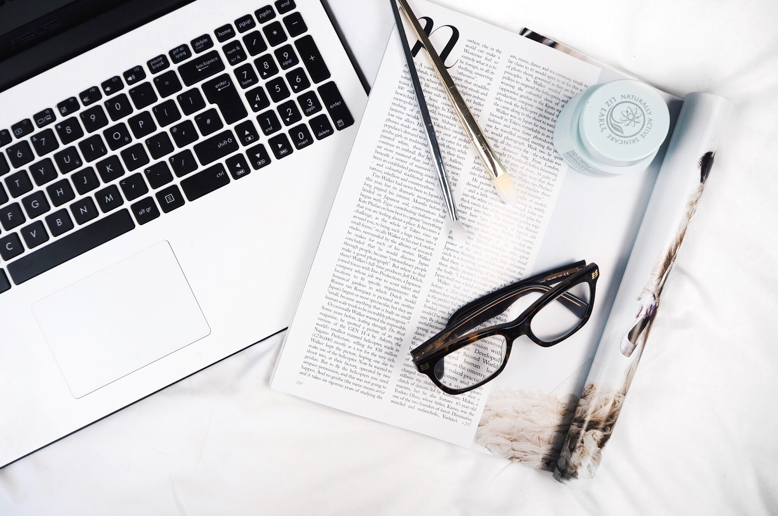 A white and black laptop with a glossy magazine, crocodile print Boots Opticians glasses, Real Techniques Bold Metals brushes and Liz Earle hydrating moisturiser flatlay photograph