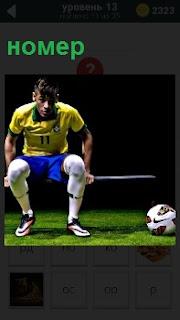 На скамейке сидит спортсмен с номером на майке и рядом лежит мяч, готовый выйти на поле