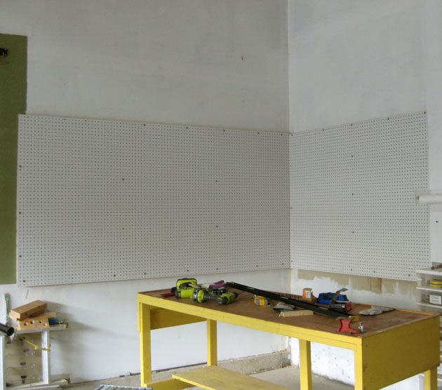Yellow bench and pegboard on garage wall