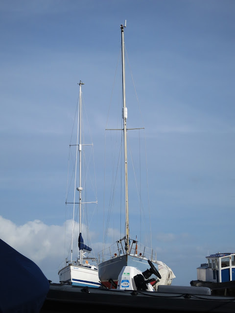 Two boats with tall masts in dry dock.