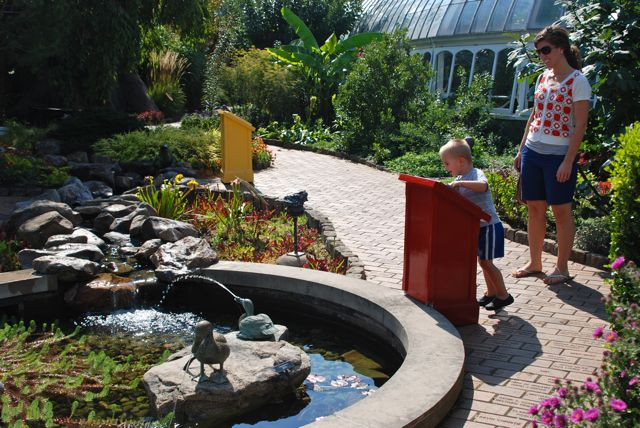 The Children's Garden is located outside between two wings of the conservatory. You can explore it in all season, but the summer the most exciting because the water is turned on. Logan loves to push the large button to make the duck spray water in this lily pond. The path goes back to an over-sized climbing stump, a maze and a little house.