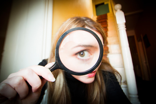 Girl looking through a magnifying glass at the viewer
