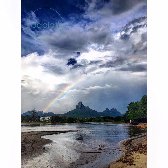 arc en ciel au dessus d'une montagne depuis la plage de tamarin à l'île maurice
