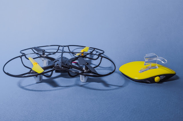 A small quad helicopter drone and a yellow and black motion controller to hold in your hand.