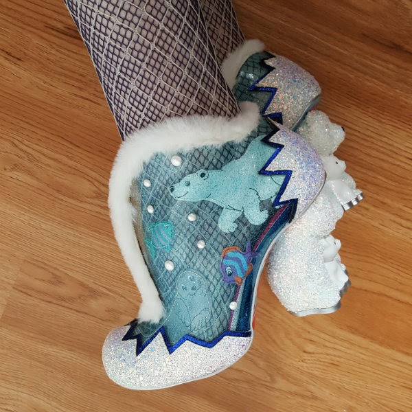 close up of blue PU shoe with applique sea animals and pearls and white fur trimmed top on foot