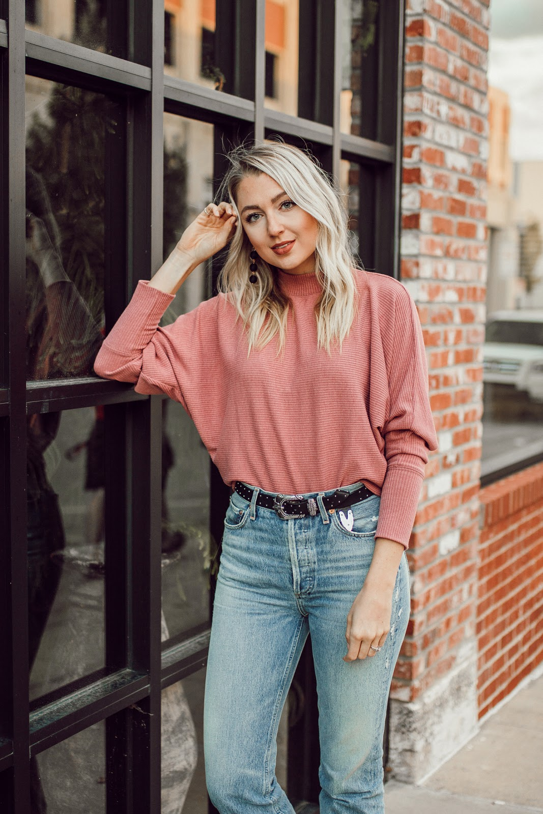 mock neck pink sweater tucked into high-waisted jeans
