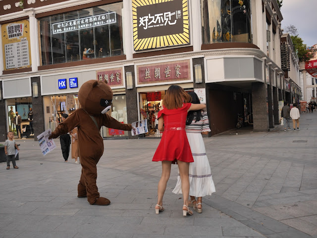 young woman hiding behind her friend from a person in a bear suit