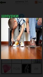 мальчик завязывает шнурки на своих ботинках, рядом взрослый мужчина