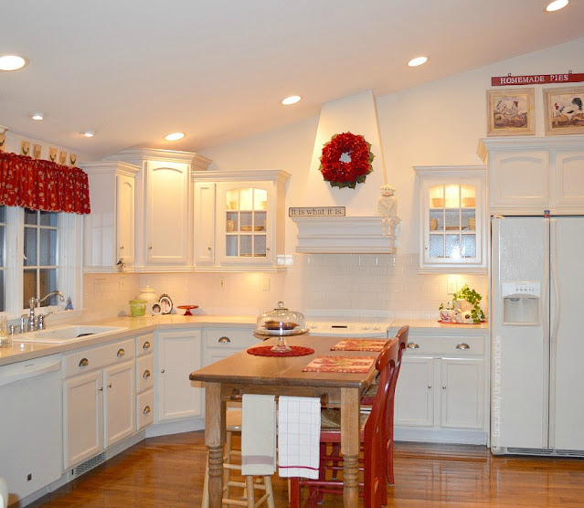 White/ Bisque  cottage style kitchen with red accents and wooden island