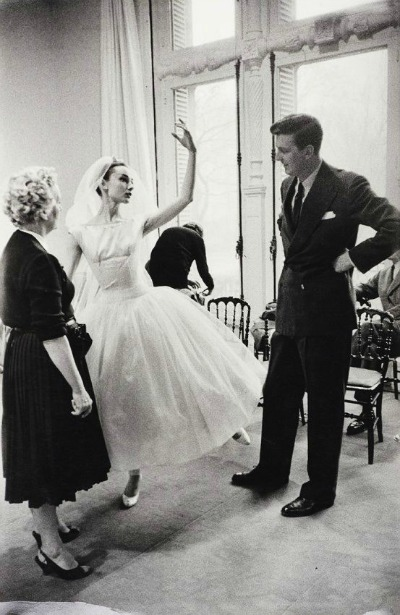 Audrey Hepburn in costume for Funny Face with Hubert de Givenchy inspecting the design