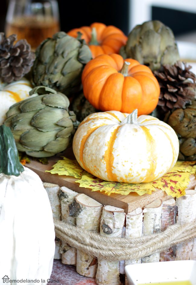 Pumpkin and dried artichokes centerpiece on table.
