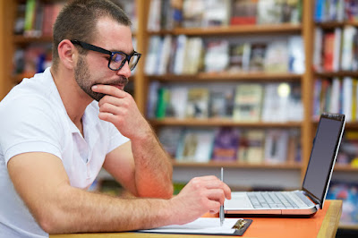 man sitting pensively at laptop in library