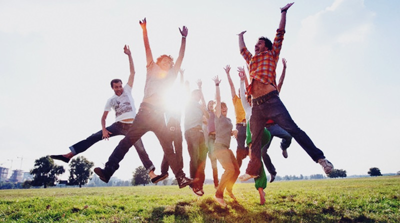 Jovens pulando de alegria no campo
