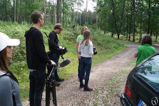 Die Autorin unterhält sich mit dem Kameramann. Rings herum stehen verschiedene Personen.