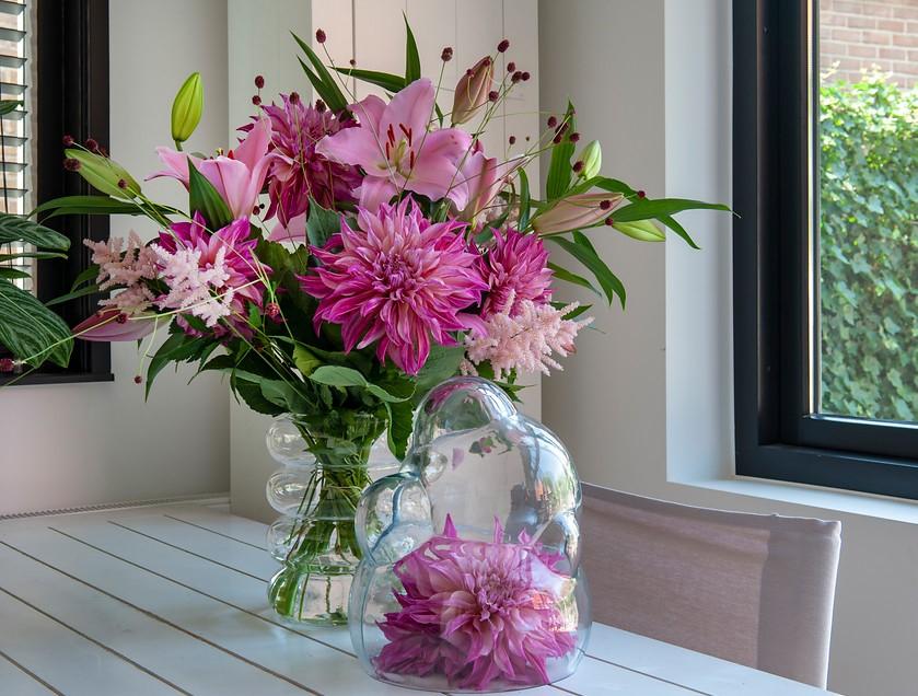 dalias y azucenas de color rosa en jarrón de cristal