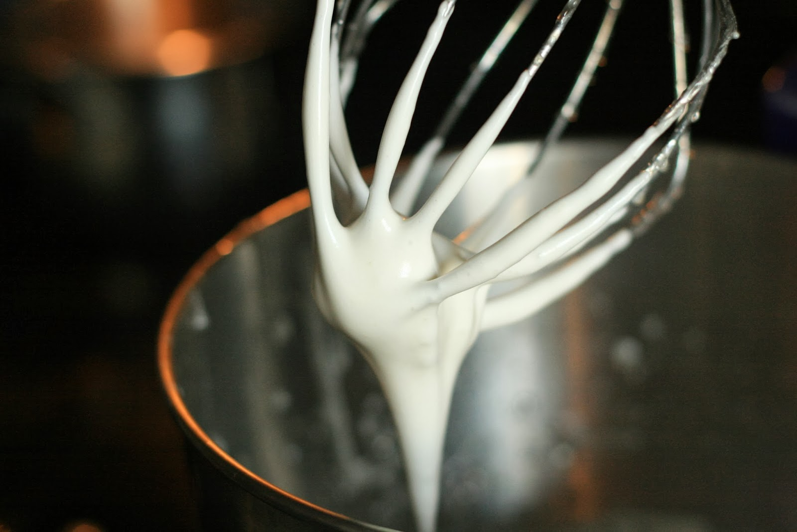 The white egg meringue mixture coating the whisk attachment of a kitchenaid stand mixer.