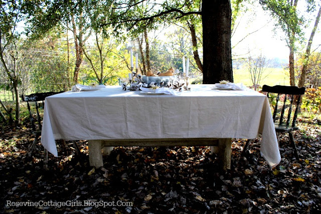 Photo of a wooden table with white tablecloth in a outdoor country setting with white china plates, a metal container with squash and candles. Fall Farmhouse Tablescape | Thanksgiving Table Centerpiece