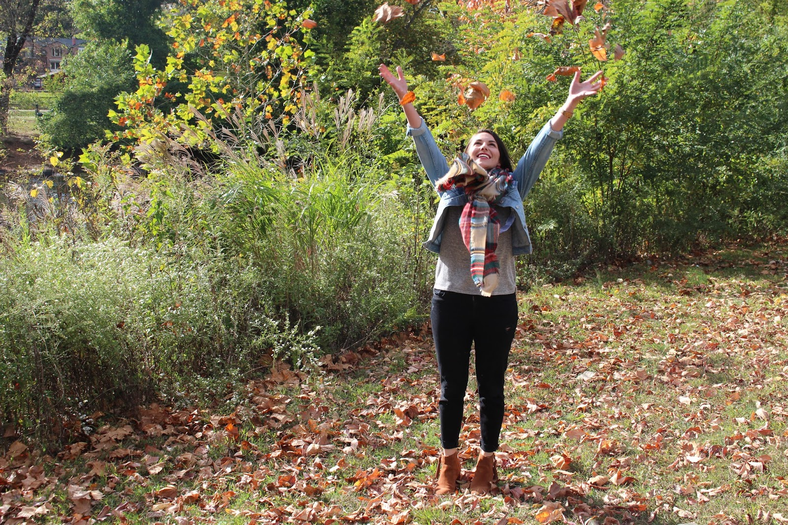 This is a picture of me in fall attire throwing leaving into the air. This was shot in Wilmington, Delaware.