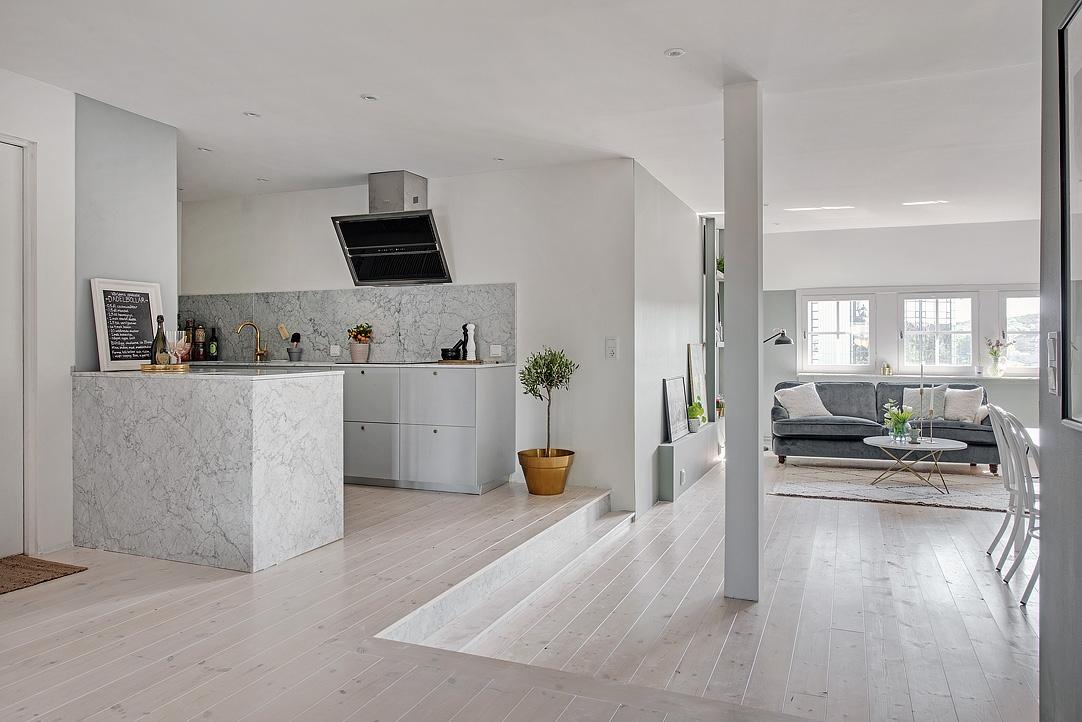 Mansarda open space con tonalità grigio verde e cucina in marmo ...