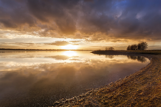 Storm clouds lit up by orange sunset light at Grafham Water