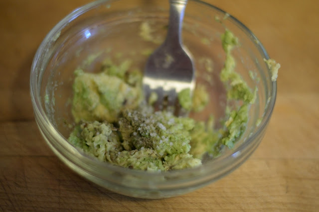 The avocado mashed in a bowl, and seasoned with salt and pepper.