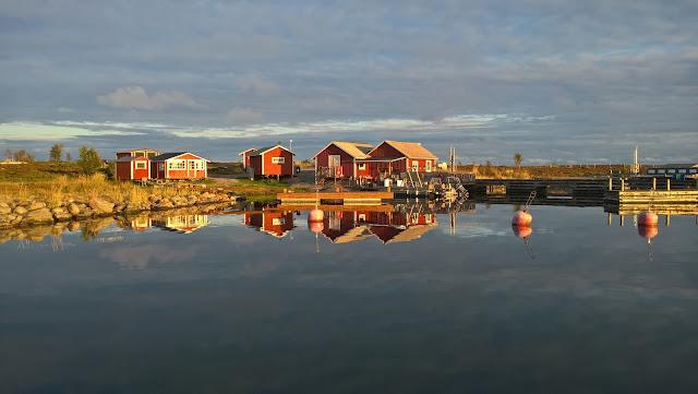 Punaisia kalastajamökkejä rannalla, peilityyni meri.