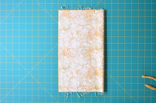 Fabric is laid out on cutting mat grid and is folded vertically with the fold on the right hand side and the two straight sides meeting at the left hand side.