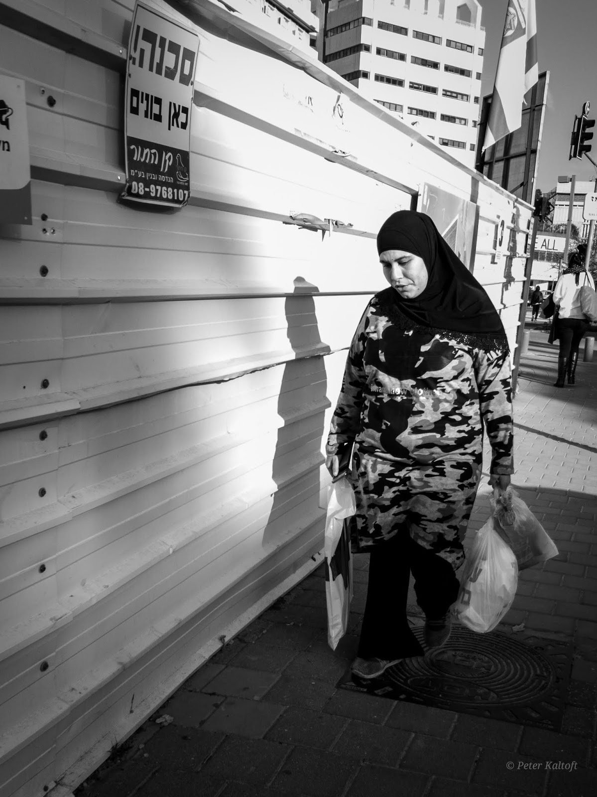 A Muslim woman passes a construction site sign, warning of danger