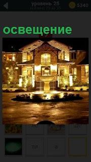 Фасад трехэтажного частного дома в вечернее время. Освещение присутствует во всех окнах  и снаружи подсвечен вход и фонтан перед ним