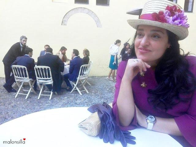 Invitada a boda de invierno con sombrero copa alta tipo chistera de flores en color buganvilla y burdeos