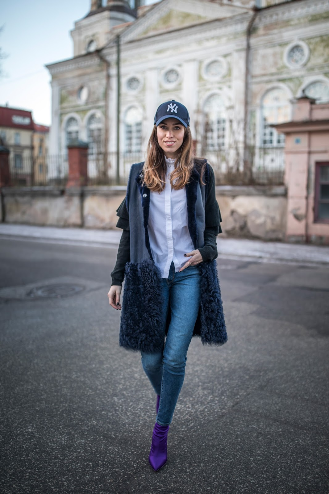 navy shearling vest over jeans cap sock boots outfit