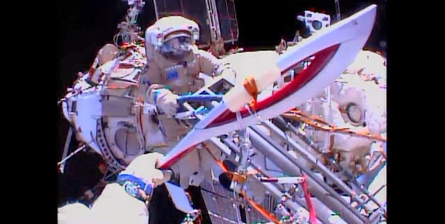 Olympic torch outside the International Space Station during Saturday's spacewalk. Image Credit: NASA TV