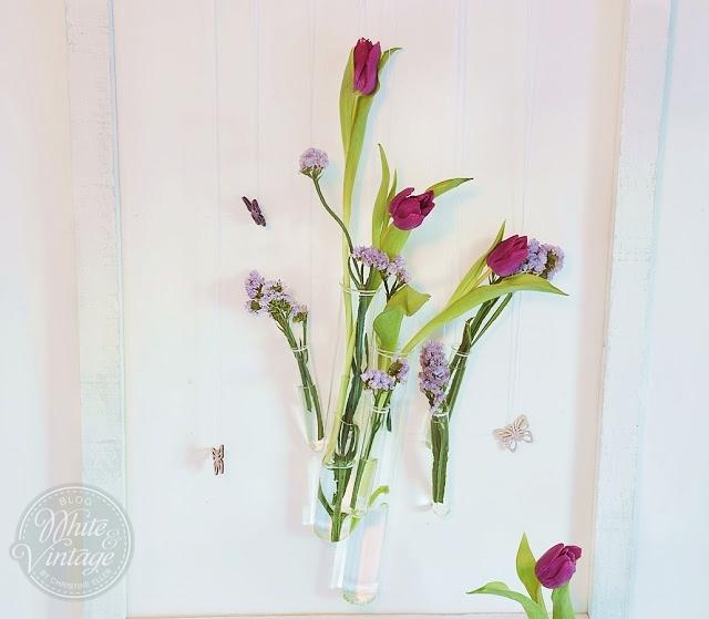 Wanddeko aus Reagenzgläsern und Blumen