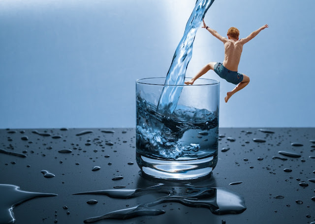 A boy jumping in to a glass of water.