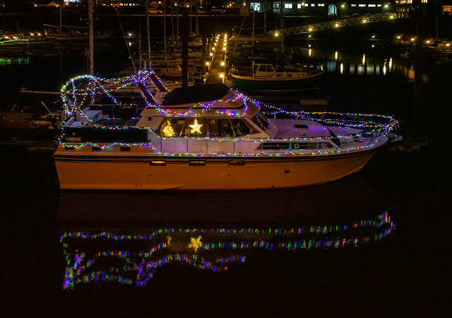 Photo of Ravensdale's Christmas light reflected in the still water at Maryport Marina in Cumbria, UK