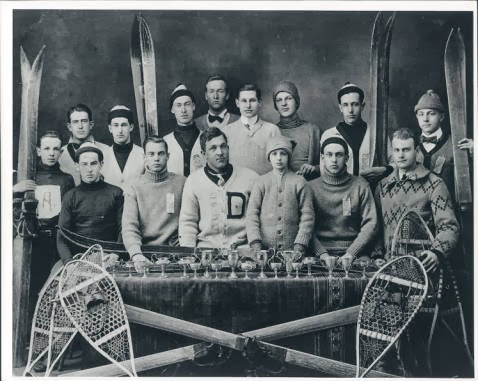 A black and white photograph of a group in winter gear. There are skis and snowshoes visible in the picture.