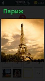 На картинке изображение символа Парижа Эйфелевая башня на фоне мрачного и пасмурного неба