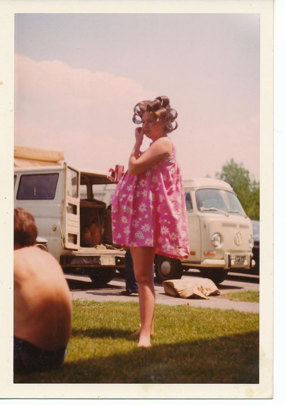 1960s snapshot of a woman in oversized hair rollers, smoking, very pregnant and wearing a short pink housedress. As Seen on TV and other stories of marketing the American Dream. marchmatron.com