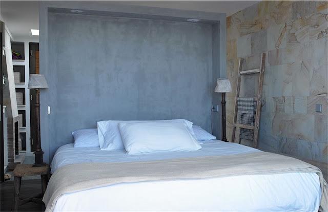 dormitorio con pared de piedra casa en ibiza chicanddeco