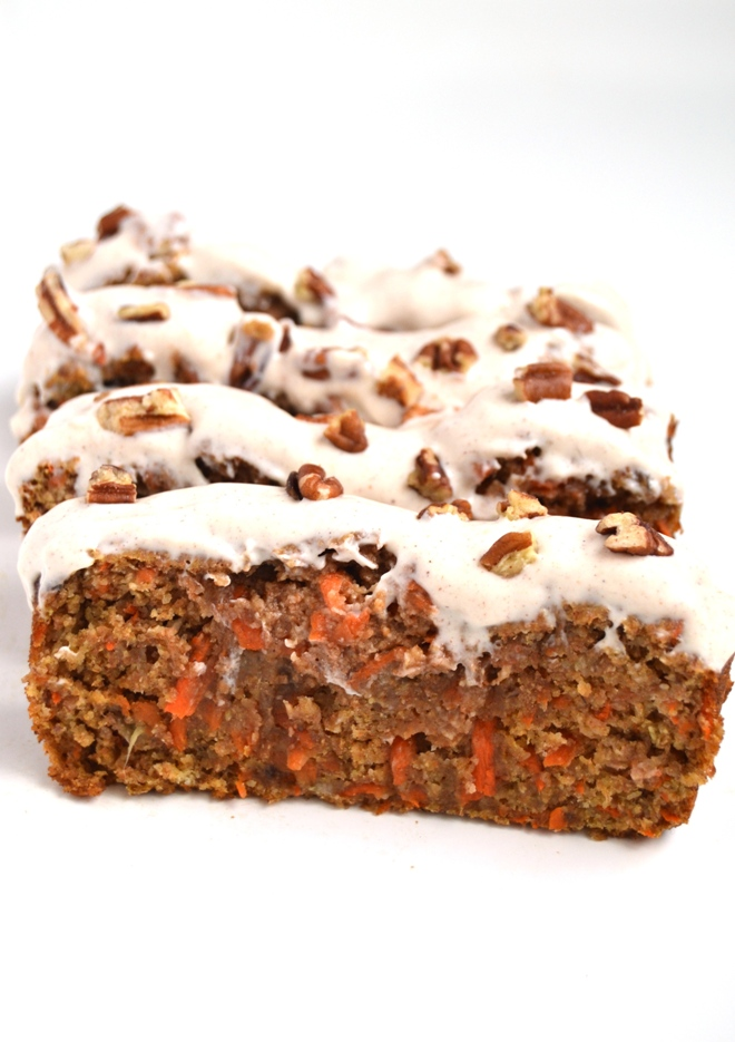 Carrot Cake Banana Bread with Cream Cheese Frosting is a moist and healthy treat that tastes like cake made with whole-wheat flour and apple sauce. It is topped with cinnamon cream cheese Greek yogurt frosting- you won't be able to stop at one slice! www.nutritionistreviews.com