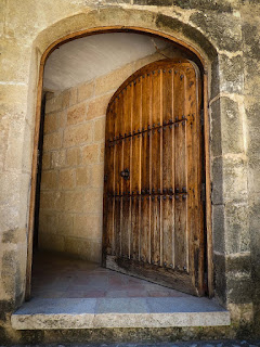 A heavy wooden door in an old stone building. The door hangs open.